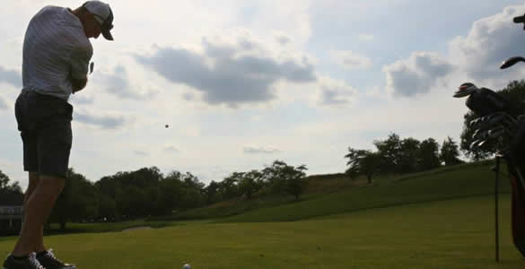 Man hitting golf ball on green